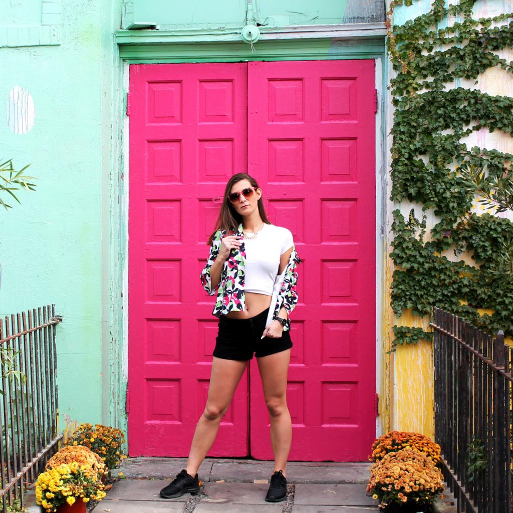 girl in front of pink doors